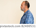 Profile view of handsome bearded Indian man against plain wall 82400531