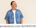 Portrait of handsome bearded Indian man against plain wall 82400549