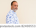 Portrait of handsome bearded Indian man against plain wall 82400553