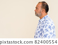 Profile view of handsome bearded Indian man against plain wall 82400554