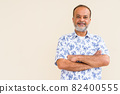 Portrait of happy bearded Indian man smiling against plain wall 82400555