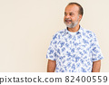 Portrait of handsome bearded Indian man against plain wall 82400559