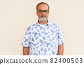 Portrait of handsome bearded Indian man against plain wall 82400563
