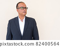 Portrait of Indian businessman thinking against plain wall outdoors 82400564