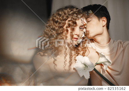 Emotional portrait of a boy and girl with flowers on their face 82535162