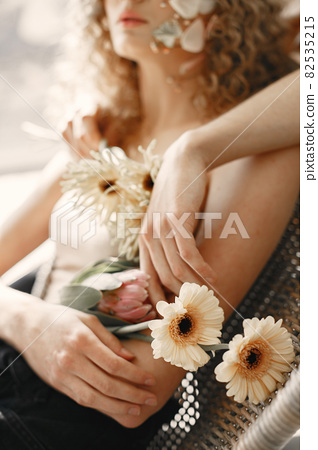 Beautiful young woman holding flowers. Tenderness and aroma. 82535215