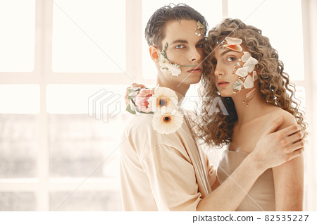 Emotional portrait of a boy and girl with flowers on their face 82535227