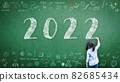 2022 Happy new year school class academic calendar with student kid's hand drawing greeting on teacher's green chalkboard for educational celebration, back to school, STEM education classroom schedule 82685434