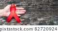 World aids day and national HIV AIDS and ageing awareness month with red ribbon on helping hand (isolated with clipping path on white background) 82720924
