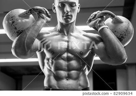Young athletic man pumping up muscles in the gym at workout. Sport and health care concept background 82909634