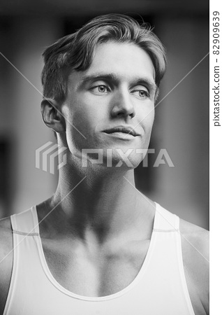Young athletic man pumping up muscles in the gym at workout. Sport and health care concept background 82909639