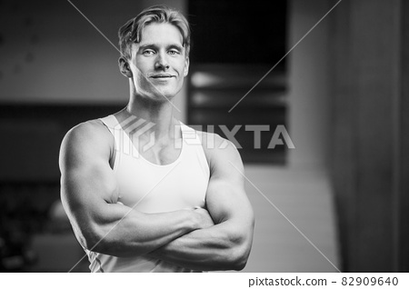 Young athletic man pumping up muscles in the gym at workout. Sport and health care concept background 82909640
