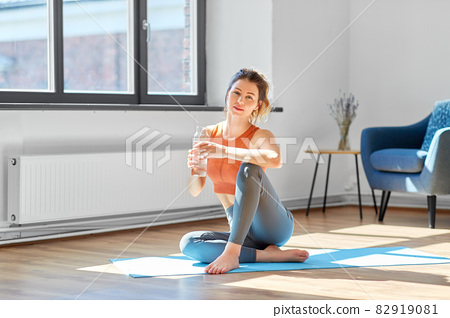 woman with water resting on yoga mat at home 82919081