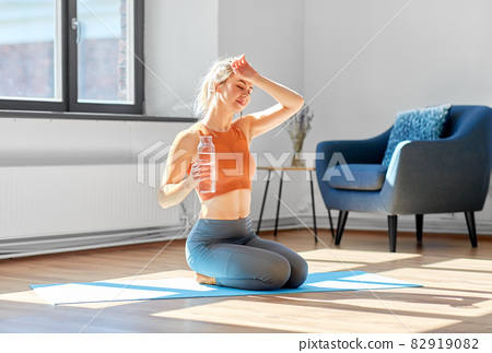 tired woman with water resting on yoga mat at home 82919082