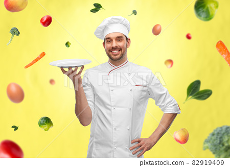 happy smiling male chef holding empty plate 82919409
