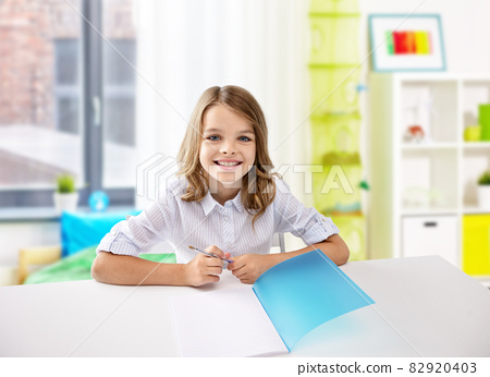 happy student girl with notebook and pen at home 82920403