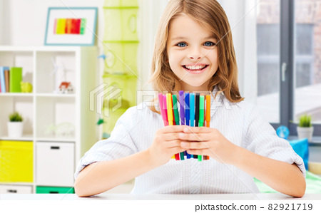 smiling student girl with felt-tip pens at home 82921719