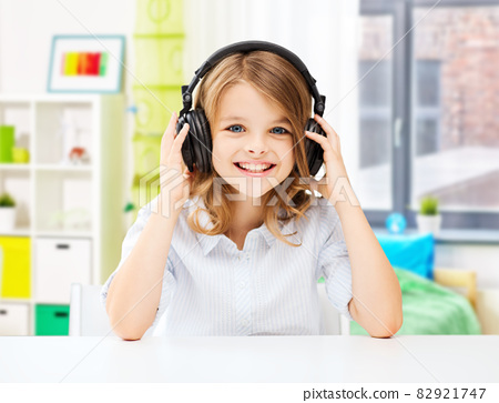 happy smiling girl with headphones at home 82921747
