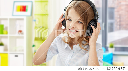 happy smiling girl with headphones at home 82921977