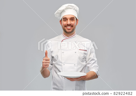happy male chef with empty plate showing thumbs up 82922482