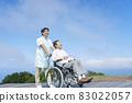 Elder caregiver and elderly person in a wheelchair 83022057