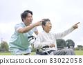 Elder caregiver and elderly person in a wheelchair 83022058