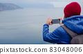 woman take photo of sea on smartphone 83048006