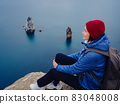 Back view of woman on shore of North sea on cold winter day. 83048008