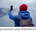 woman take photo of sea on smartphone 83048010