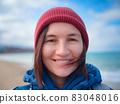 woman take photo of sea on smartphone 83048016