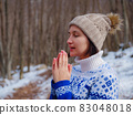 Beautiful woman standing among trees in winter forest 83048018