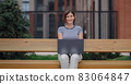 student working at laptop sit down on bench on urban city street. 83064847