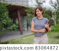 woman walking with laptop in modern park street 83064872