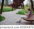 woman in modern park spending her break time 83064876