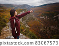 Happy tourist with outstretched arms, freedom and happiness, reaching in the mountains 83067573