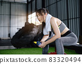 Woman wearing sport sitting and resting after exercise in fitness gym holding drinking water. Healthy people concept 83320494